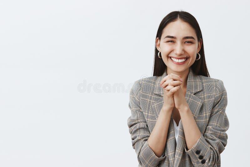 微笑时髦的愉快的欧洲女朋友水平的射击夹克的,一起扣紧手在胸口和快乐 免版税库存图片