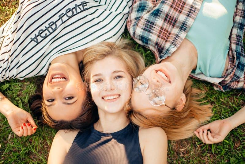 微笑时髦的朋友顶视图看照相机和,当说谎在草时 免版税库存照片