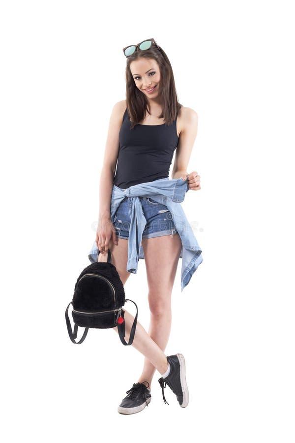 微笑时髦的现代夏天的衣裳的嬉戏的迷人的逗人喜爱的少女摆在和 免版税库存图片