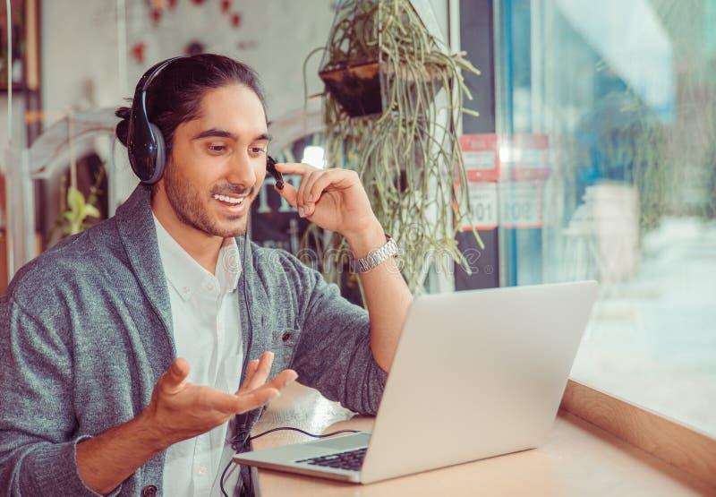 微笑有视频聊天对膝上型计算机屏幕的人,解释某事 免版税库存图片
