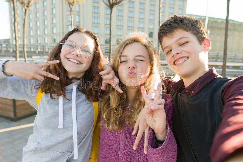 微笑朋友青少年的男孩和两个的女孩画象,做滑稽的面孔,显示胜利标志在街道 库存图片