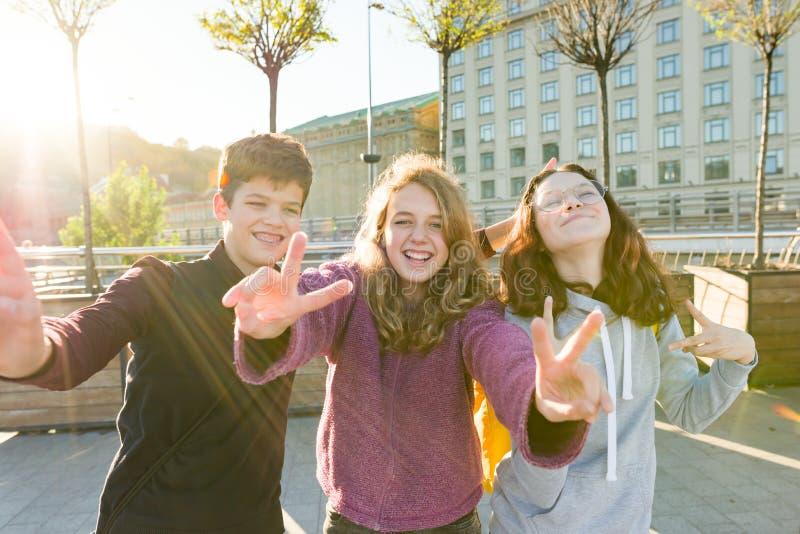 微笑朋友青少年的男孩和两个的女孩画象,做滑稽的面孔,显示胜利标志在街道 图库摄影