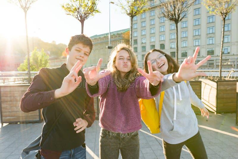 微笑朋友青少年的男孩和两个的女孩画象,做滑稽的面孔,显示胜利标志在街道 免版税库存照片