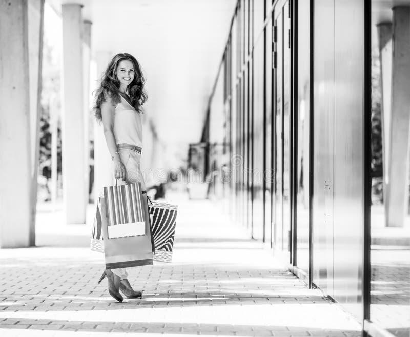 微笑棕色毛发的妇女拿着五颜六色的购物带来 免版税库存图片