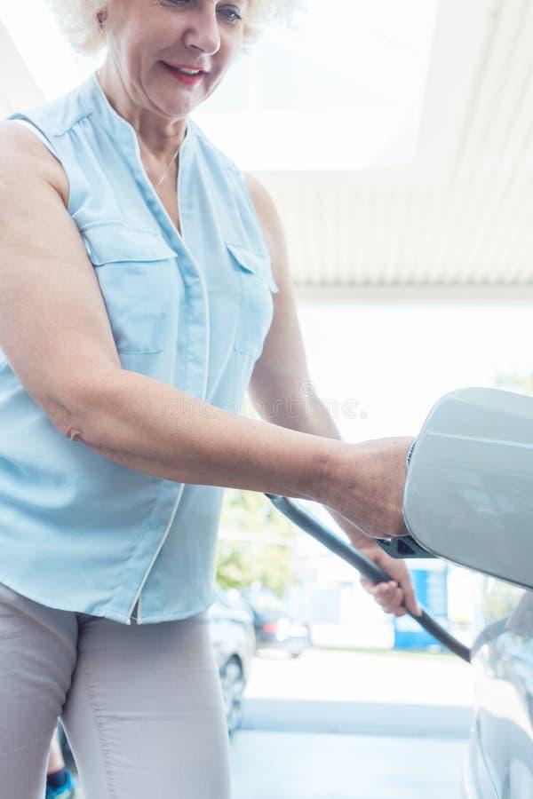 微笑活跃资深的妇女,当填装她的汽车时汽油箱  图库摄影