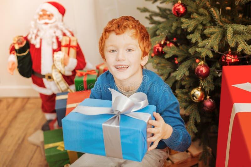 微笑激动的红头发人的孩子,当拿着他的圣诞节礼物时 免版税库存照片