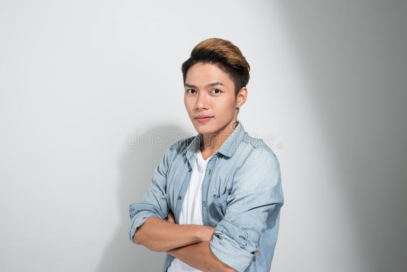 微笑牛仔裤的衬衣的亚裔确信的年轻帅哥保持胳膊横渡和,当站立反对白色背景时 库存图片
