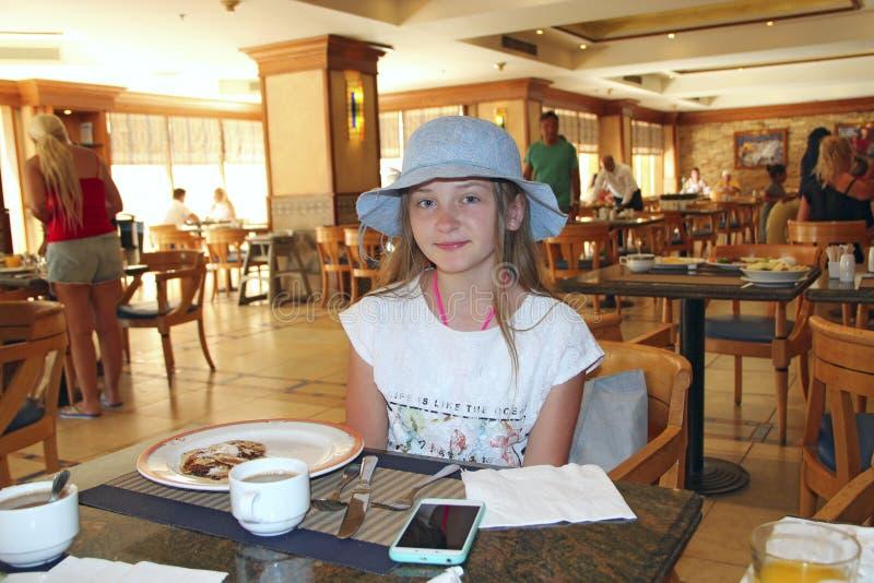 微笑现代的孩子,当坐在餐馆时 摆在的帽子的女孩,当吃时 免版税图库摄影
