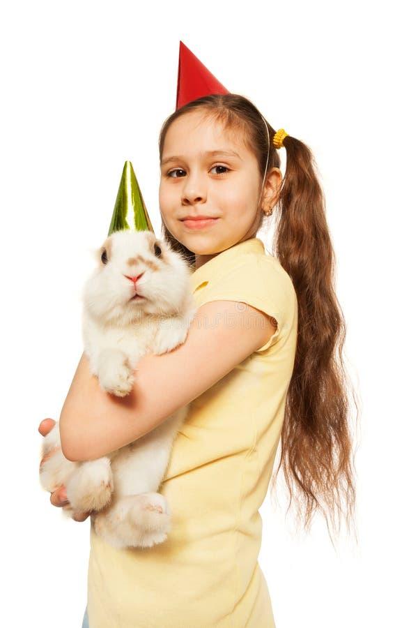 微笑生日的女孩拿着毛茸的当前兔宝宝 免版税图库摄影