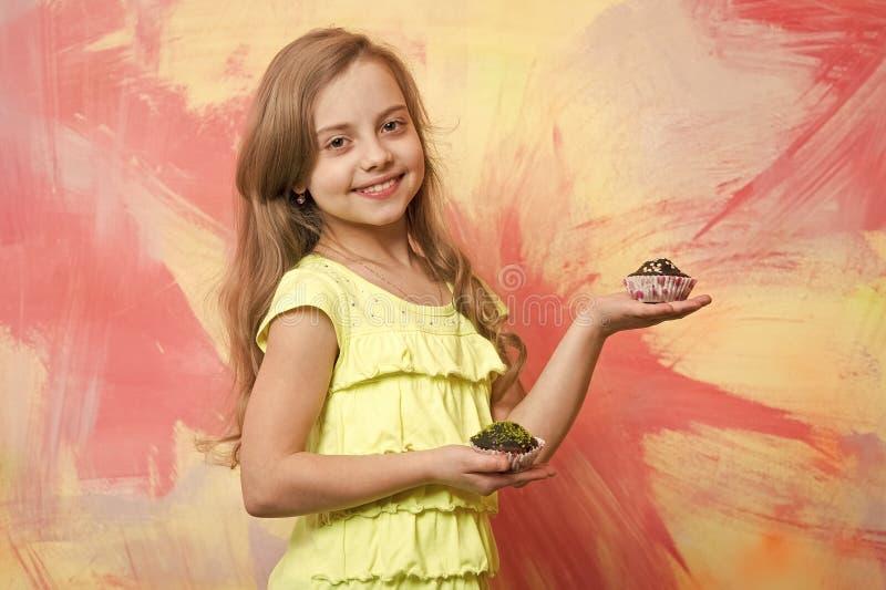 微笑用杯形蛋糕的女孩在手上 免版税库存照片