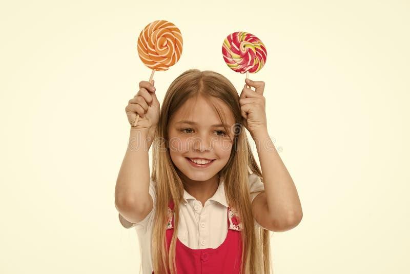 微笑用漩涡焦糖的滑稽的女孩 小孩微笑用在白色隔绝的棍子的糖果 甜点和极端 库存图片