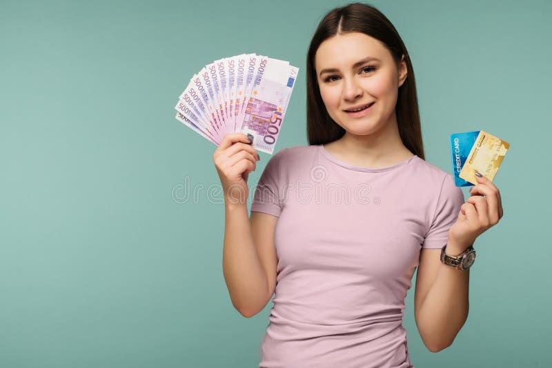 微笑白种人深色的妇女20s照片,当拿着欧元现金信用卡和爱好者被隔绝在蓝色背景时 库存照片