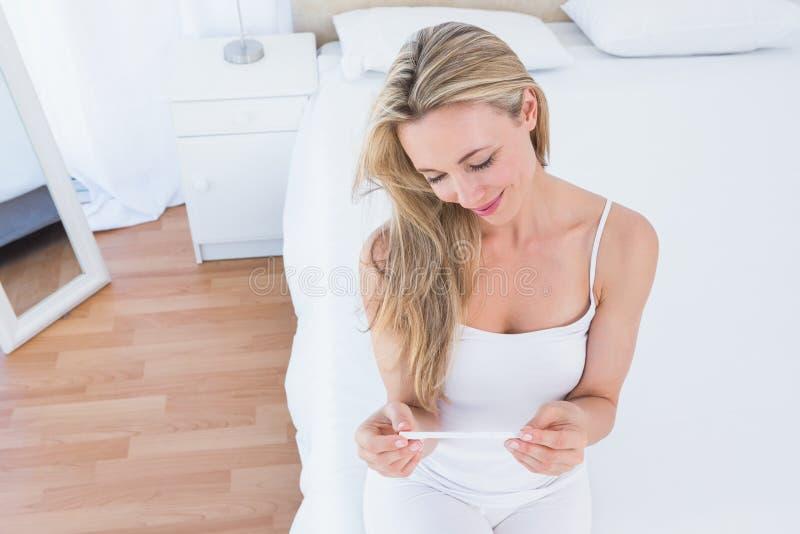 微笑白肤金发看她的妊娠试验 免版税库存照片