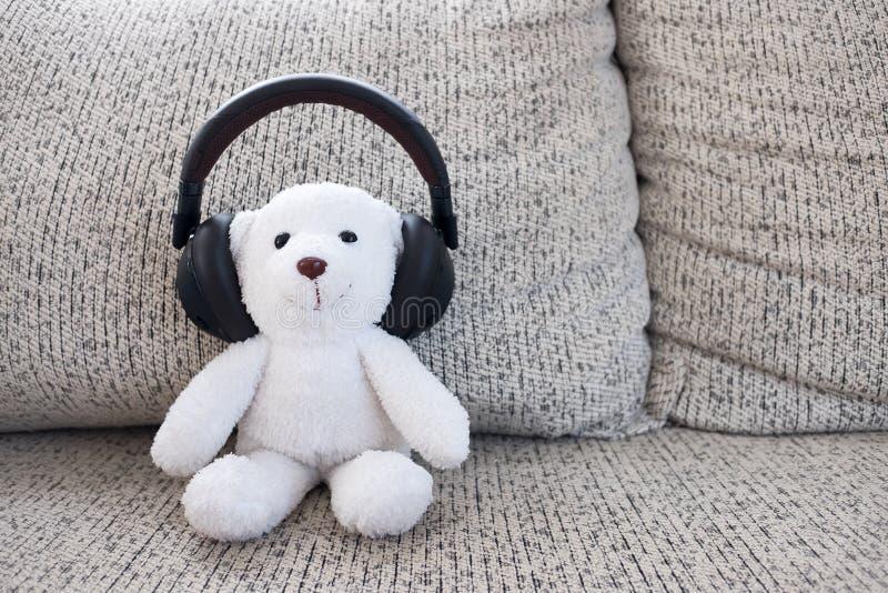 微笑白色玩具熊坐沙发和佩带的耳机 免版税库存图片