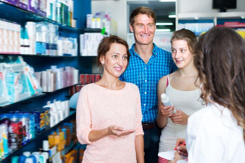 微笑的三口之家咨询的药剂师 库存照片