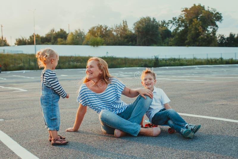 微笑的三口之家在一个停车场 库存图片