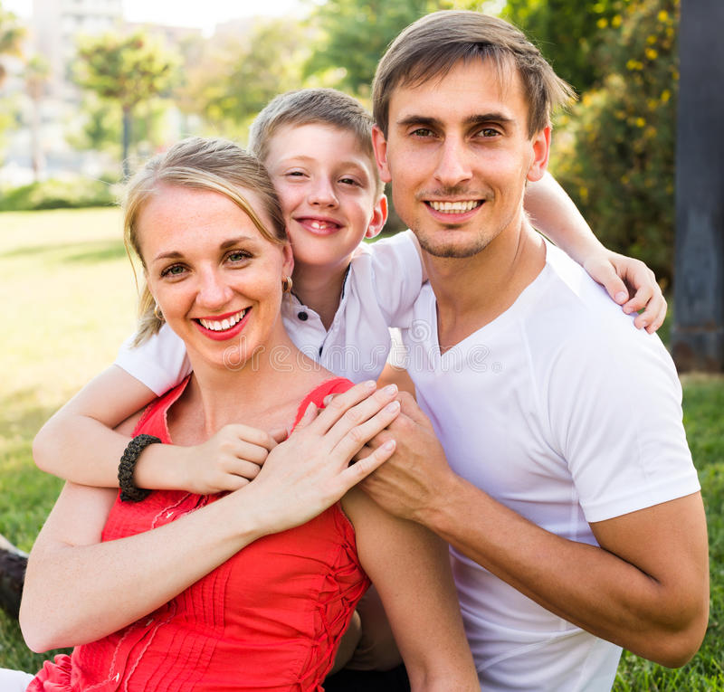 微笑的三口之家在绿色草甸 免版税库存图片