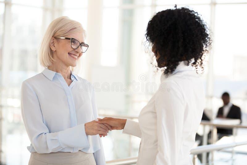 微笑的不同的女性同事握手会议在走廊 免版税库存照片
