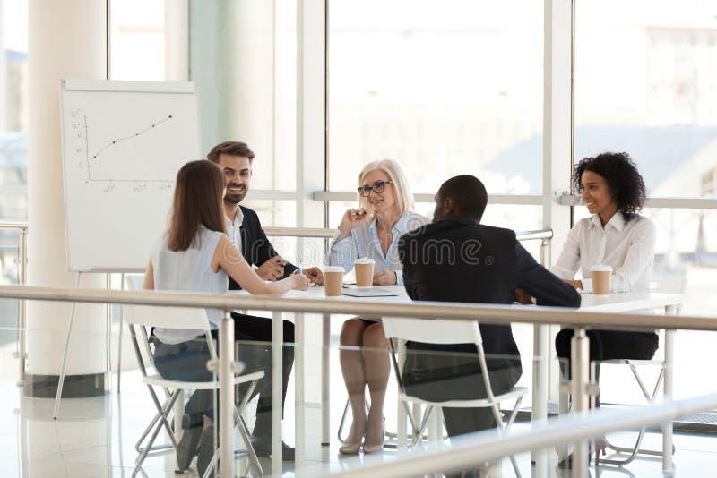 微笑的不同的雇员谈话在会议的会议桌上 库存图片