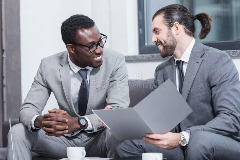 微笑的不同种族的商务伙伴坐长沙发和谈话 免版税图库摄影