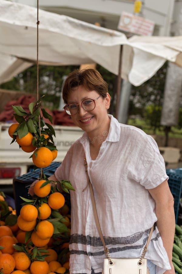 微笑的中年妇女在杂货市场上 免版税库存照片