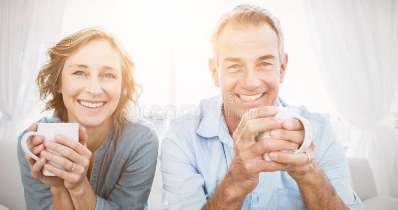 微笑的中部变老了夫妇坐食用的长沙发咖啡 库存照片