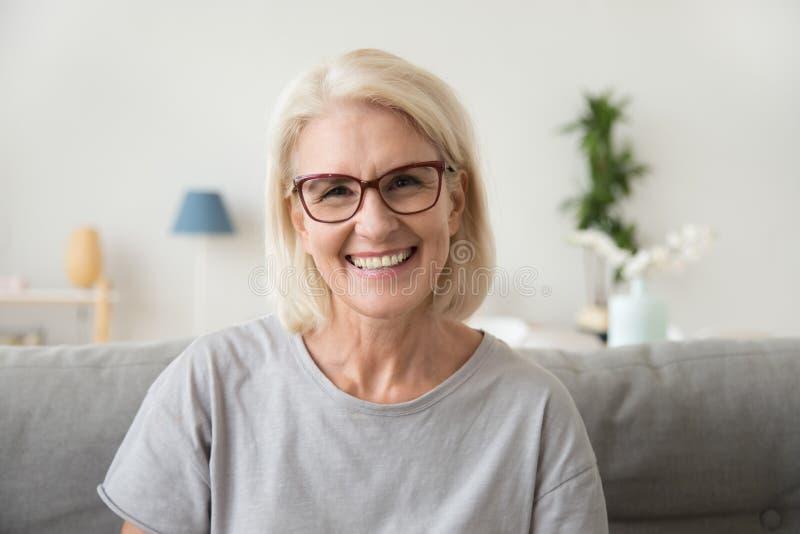 微笑的中部变老了看照相机的成熟灰发的妇女 免版税库存图片