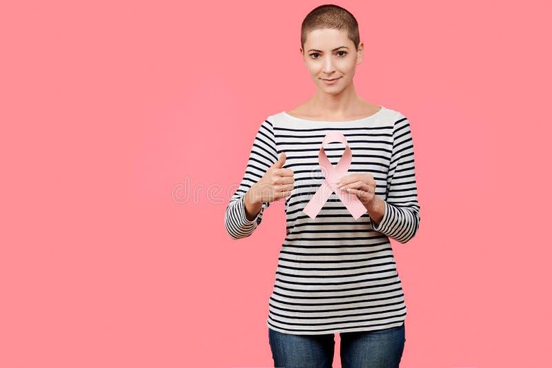 微笑的中间30s妇女,癌症幸存者,拿着桃红色乳腺癌了悟丝带和显示赞许 免版税库存照片