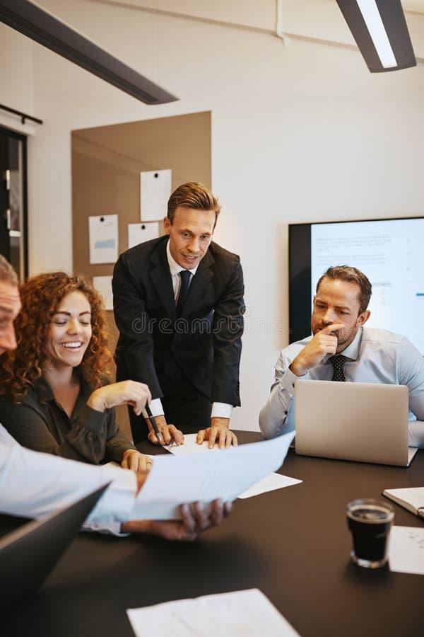 微笑的买卖人谈论文书工作在办公室boardro 免版税库存照片