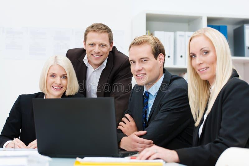微笑的事务合作在工作在办公室 库存照片