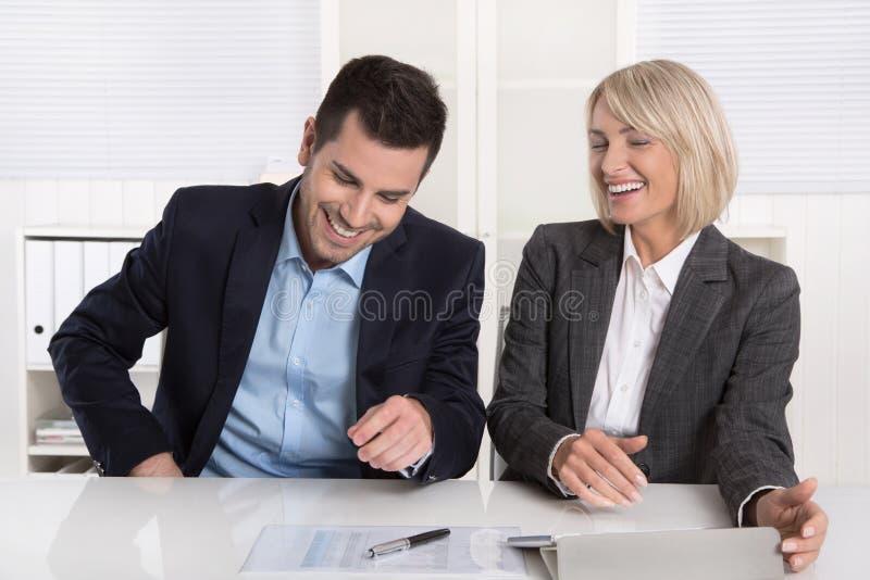 微笑的事务合作获得乐趣在办公室:每日忙碌骗局 免版税库存图片