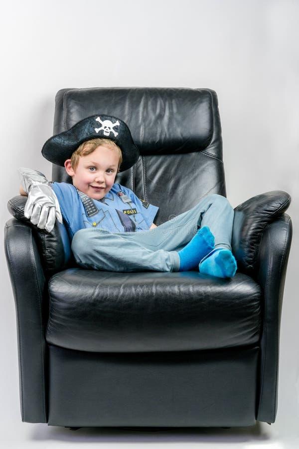 微笑的五岁的男孩在海盗装饰了,并且警察服装在一把黑皮革扶手椅子坐并且laze 库存图片