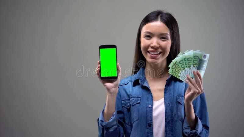 微笑的亚洲妇女藏品智能手机和欧元,在网上运作,cashback 库存图片