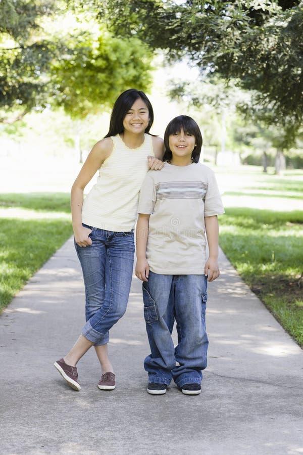 微笑的亚裔兄弟照相机姐妹 免版税库存照片