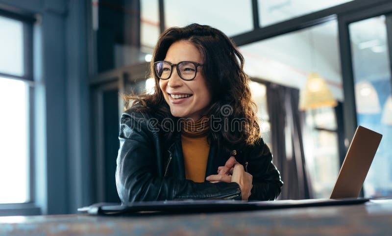 微笑的亚裔女实业家在办公室 免版税库存照片