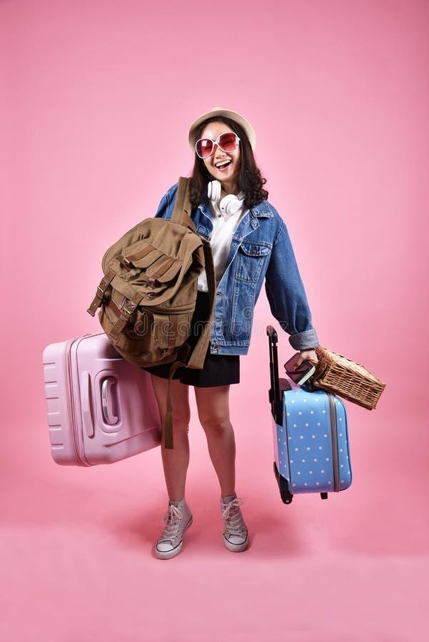 微笑的亚裔妇女旅客运载全部行李,有愉快的旅游的女孩快乐的假日旅行,许多行李 免版税库存图片