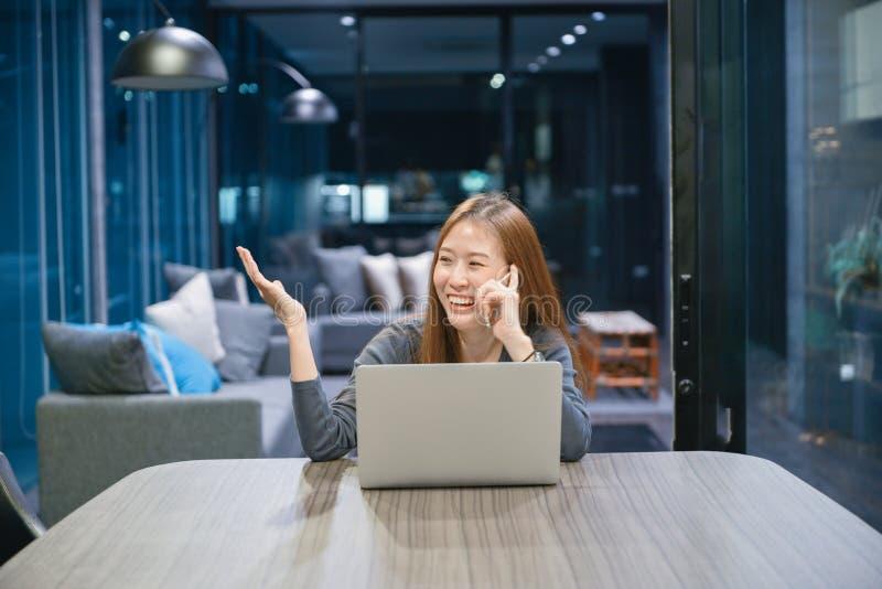 微笑的亚裔妇女谈话在电话,使用膝上型计算机在晚上, 库存图片