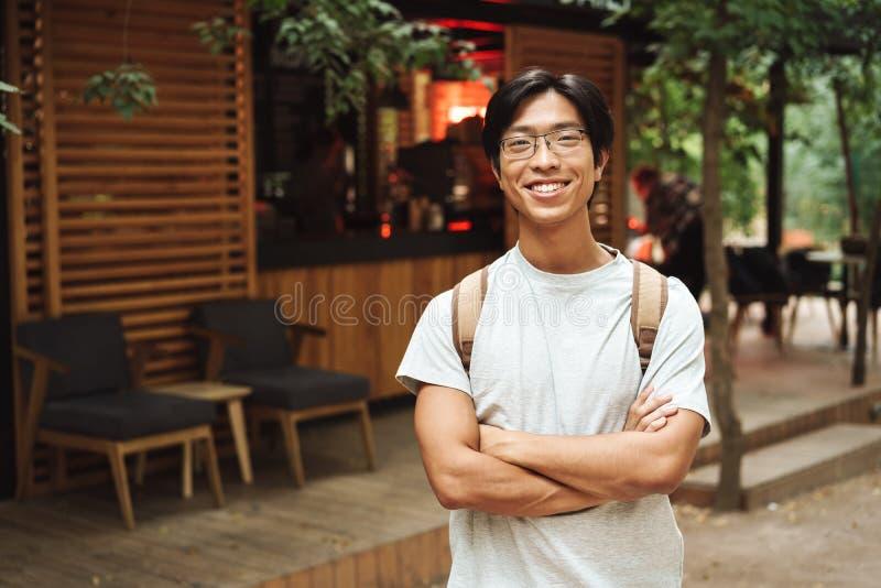 微笑的亚裔学生人佩带的背包 免版税库存照片