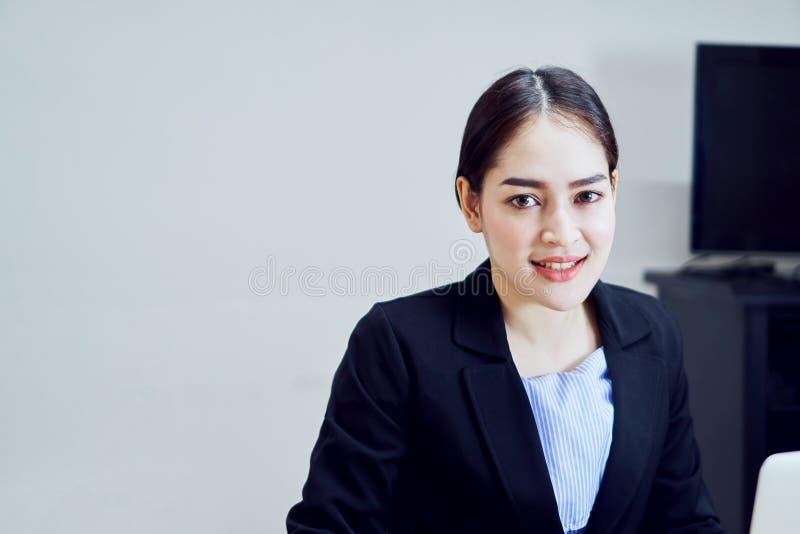 微笑的亚裔少妇一套黑衣服的女商人办公室 图库摄影
