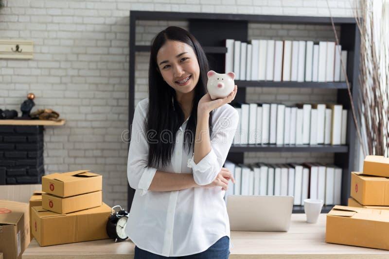 微笑的亚裔少妇画象有存钱罐和纸板箱站立的 免版税库存图片