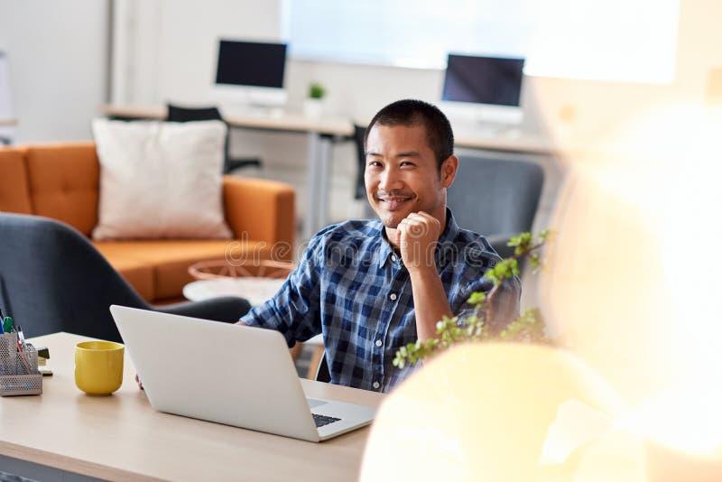 微笑的亚裔建筑师在工作在一个现代办公室 免版税库存图片