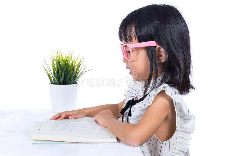 微笑的亚洲中国小女孩阅读书 库存照片