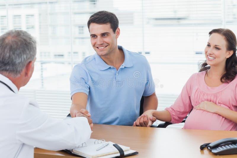 微笑的人与他的医生握手,当拿着他的expe时 免版税库存图片