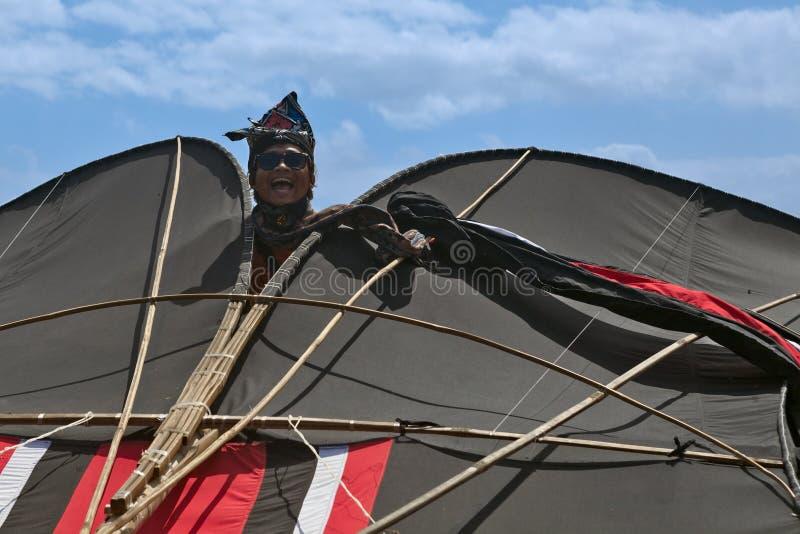 微笑的人偷看从一只巨大的五颜六色的风筝的后面 库存图片