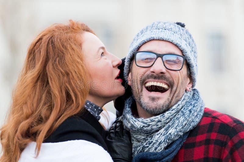 微笑的人听妇女 非常从妇女故事的愉快的人 妇女在玻璃耳语供以人员 关闭人张的嘴 免版税库存图片