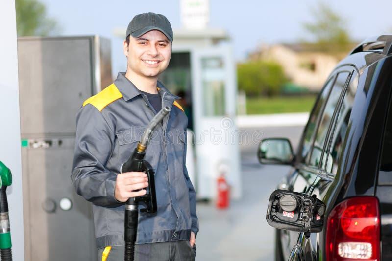 微笑的人在加油站的工作 免版税库存照片