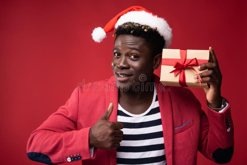 微笑的人拿着有红色丝带的礼物盒 免版税图库摄影