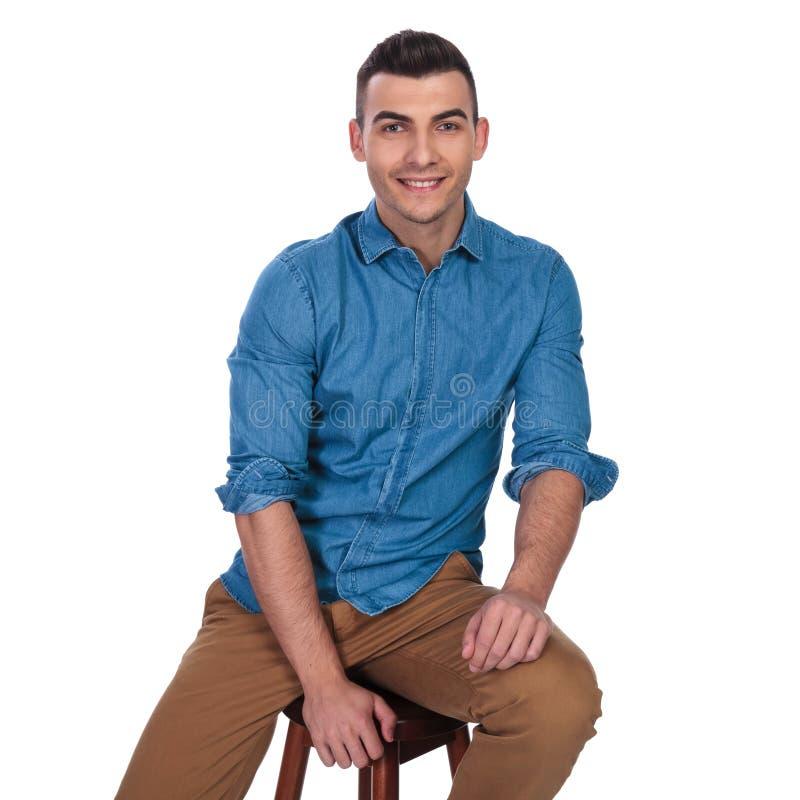 微笑的人画象坐木椅子 库存图片