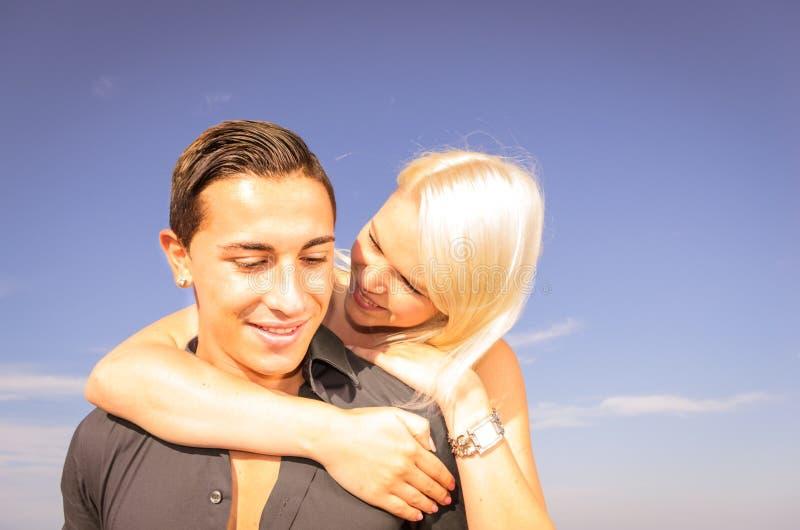 年轻微笑的人肩扛他美丽的女朋友 库存图片
