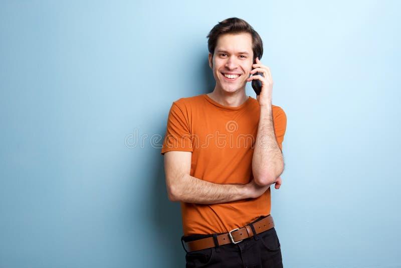 微笑的人谈话在支持蓝色墙壁的手机 免版税图库摄影